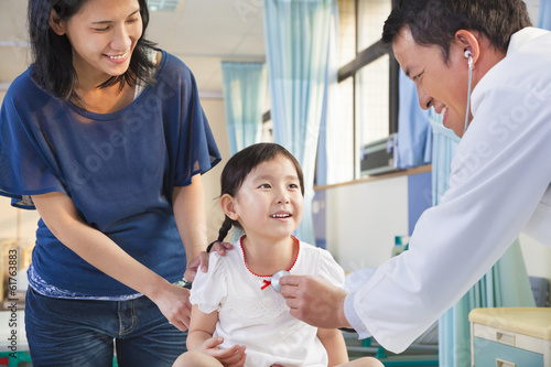 pediatrician examining little girl , her mother beside her