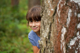 Little girl peeking out from behind a tree trunk