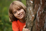 Boy in red T-shirt peeking out from behind a tree trunk