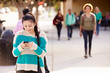 Female Student Walking To High School Using Mobile Phone