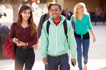 Male And Female Students Walking To High School
