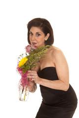 older woman black dress bend smell flowers
