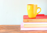 yellow cup of coffe on old vintage books