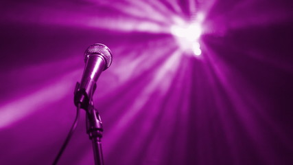 Microphone on stage against the rotating purple disco ball.
