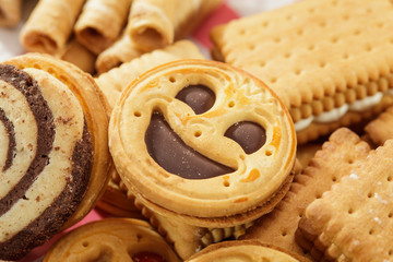 Rounnd smiling cookie on a pile of biscuits