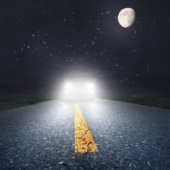 Night driving on an asphalt road towards the headlights