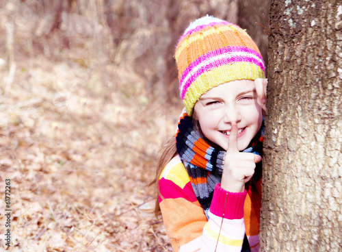 Little girl leaning on the tree. Spending a nice time in nature