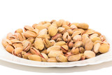 close up of a plate of pistachio nuts on white background