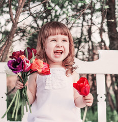 happy girl with tulips on white wooden bench