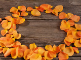 orange roses petals on wooden table