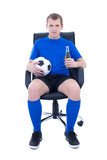 young attractive man in football form sitting with ball and bott