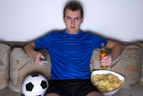 football supporter in uniform sitting in living room and watchin
