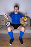 emotional football supporter watching tv with beer and chips