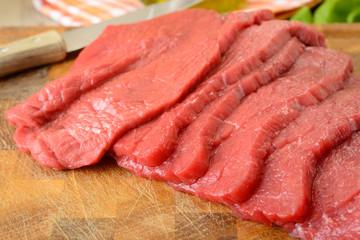 Fettine di carne di manzo crude sul tagliere di legno