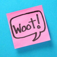 The word Woot! written in a speech bubble on a pink sticky note
