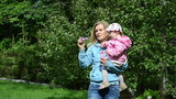 woman with daughter spend time in park blowing big soap bubbles