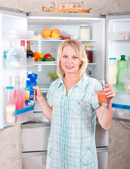 Young beautiful girl takes food from the refrigerator.