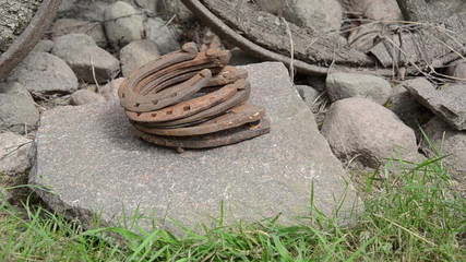 Hand put stack of retro rusty horse shoes on big stone