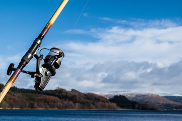 Fishing reel and rod with sea, sky and mountain