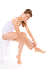 Skin care. Pretty woman removing hair from her legs, isolated