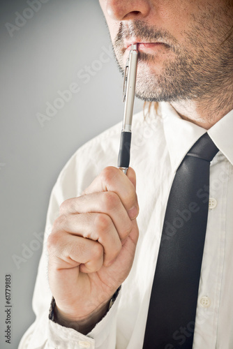 Businessman thinking with pencil in his mouth