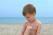 sad little boy on a sand beach