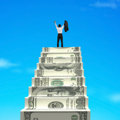Businessman cheering on top of money stairs
