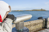 woman looking to Dalkey island by binoculars