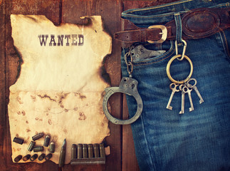 background in the style of the American West. Handcuffs in jeans