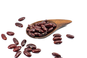 Dried red beans on a wooden spoon with a shallow depth of field