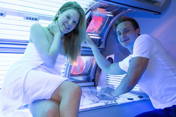 Employee in a solarium counseling customer at tanning bed