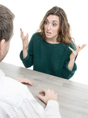 Young man and woman in argument around table