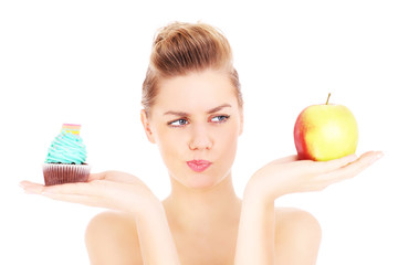 Woman trying to make a decision between cupcake and apple