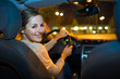 Pretty young woman driving her new car at night