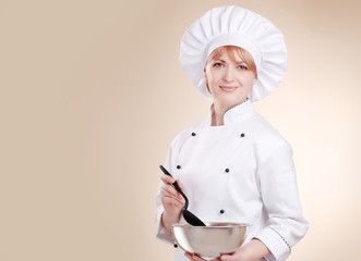 Smiling female chef with bowl and mixer