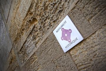 Plaque de monument historique sur un mur en pierres