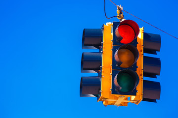 A red traffic light with a sky blue background