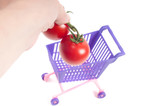 Hands putting tomatoes into shopping-cart