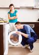 Woman  watching as worker repairing washing machine