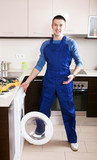 Service worker repairing washing machine