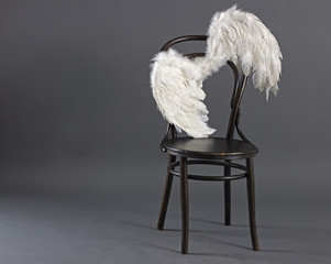 White angel wings hanging lonely on retro chair.
