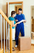 happy postman in uniform delivered a parcel to woman at home