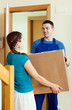 Smiling young delivary person in uniform delivered a parcel to