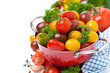 Assorted cherry tomatoes and greens in a colander, isolated