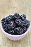 bowl of fresh blackberries on a wooden background close-up