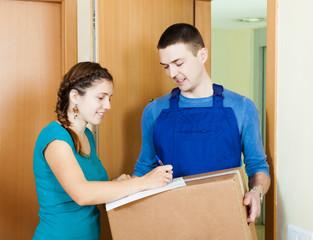 Postman in uniform delivered parcel to girl