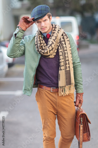 fashion man holding his hat as a greeting