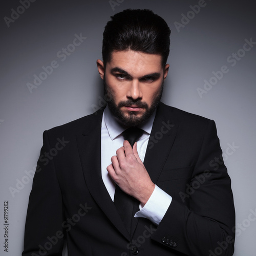 young fashion man fixes his tie
