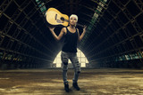 Young woman posing with acoustic guitar in abandoned factory
