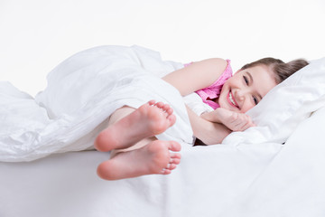 Adorable happy little girl in pink nightie awake.